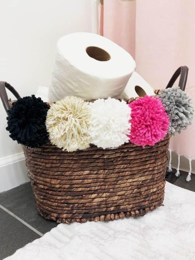 pom pom basket filled with toilet paper